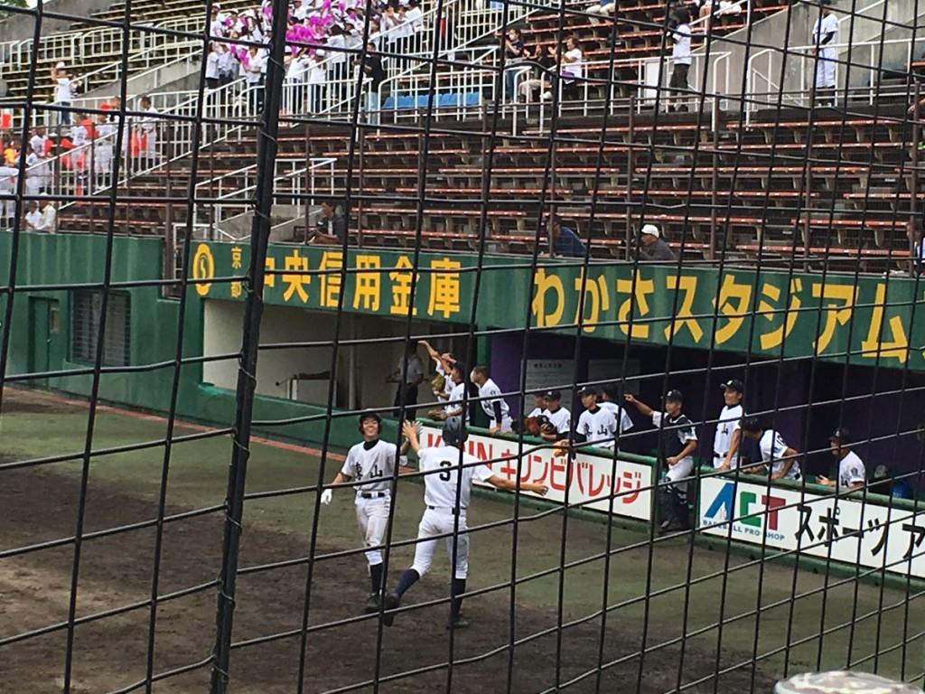 3点目のホームを踏んだ田中選手(背番号3)を迎える東山ベンチ