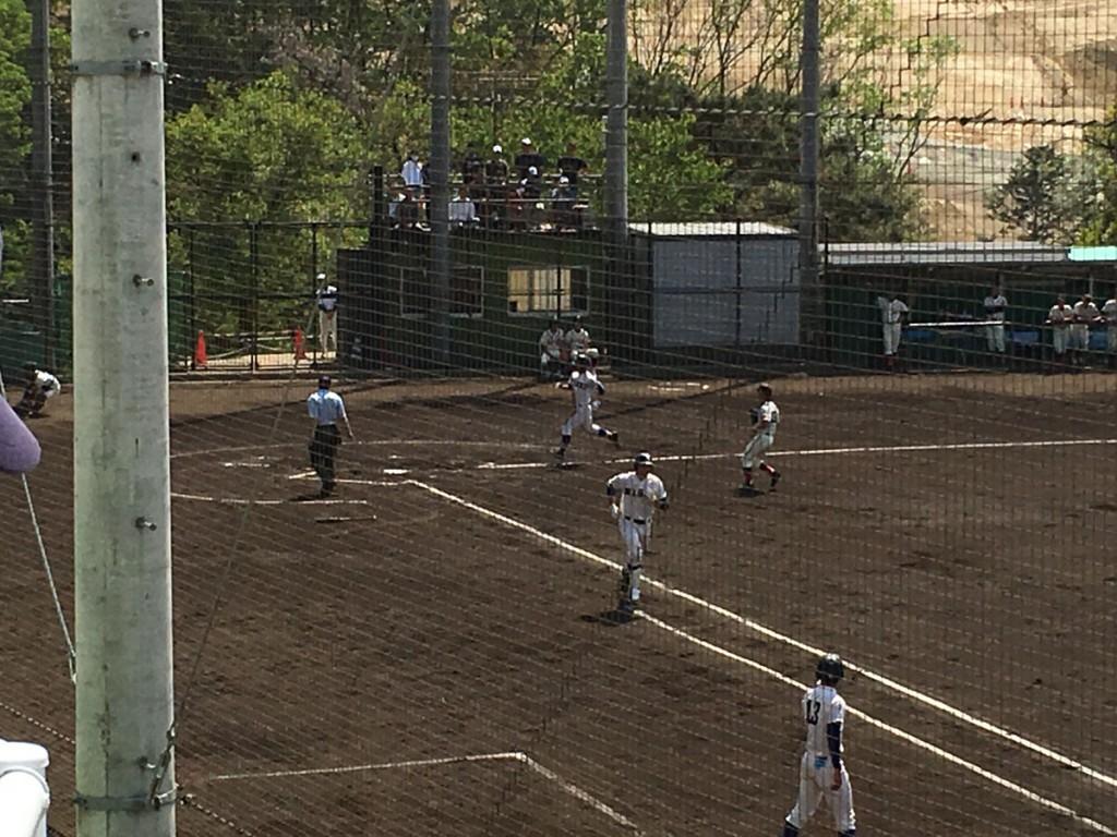 一塁へ向かう安田選手と、ホームインする石田選手(奥)
